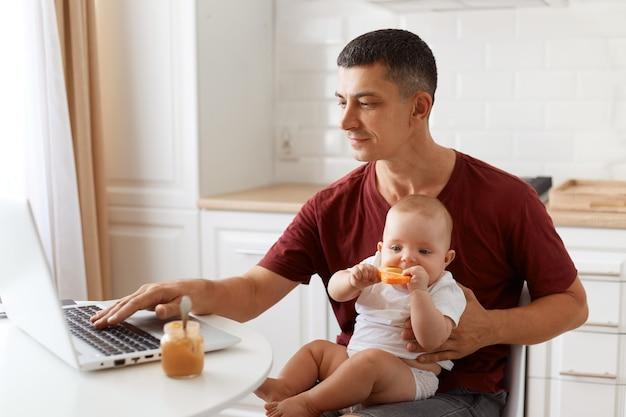 Widok z boku portret atrakcyjna brunetka mężczyzna freelancer na sobie bordową koszulkę w stylu casual, pracy i opieki nad jego małą córeczką, pisania na komputerze przenośnym.