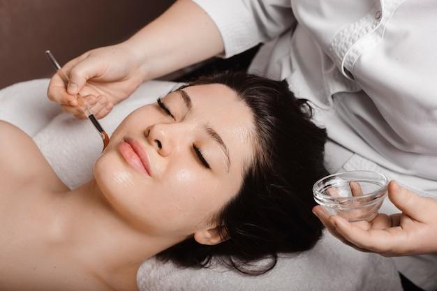 Widok z boku portret atrakcyjnej kobiety opierającej się na łóżku spa z zamkniętymi oczami, mającej maseczkę przeciwstarzeniową z kwasem hialuronowym, wykonaną przez kosmetologa.
