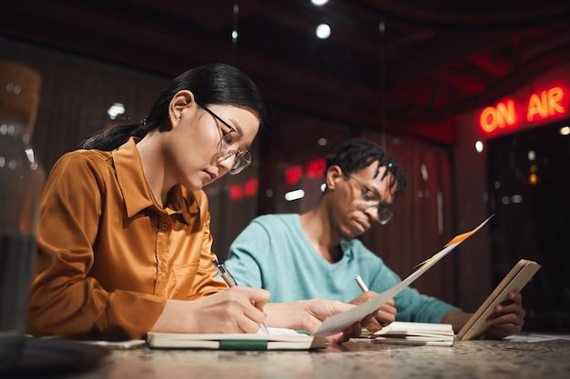 Widok z boku portret azjatyckich bizneswoman pracuje do późna w ciemnym biurze z afrykańskim kolegą