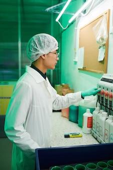 Widok z boku portret azjatyckiego pracownika noszącego odzież ochronną pracującego w laboratorium bio oświetlonym zielonym światłem