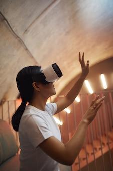 Widok z boku portret azjatyckiej kobiety noszącej sprzęt vr i gestykulującej, ciesząc się wciągającą rzeczywistością w futurystycznym wnętrzu