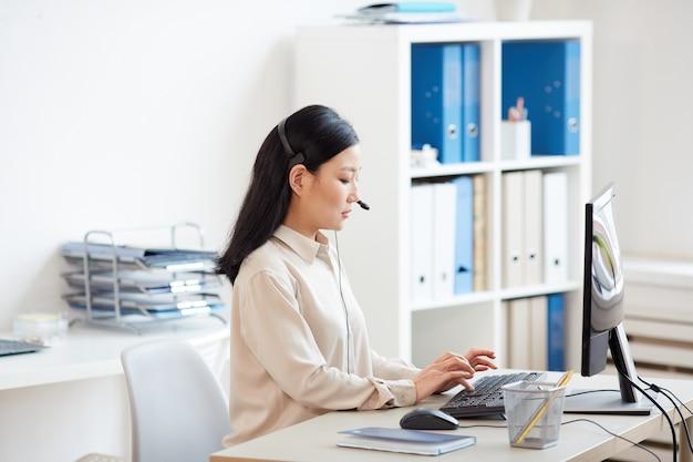 Widok z boku portret azjatyckiej kobiety noszącej zestaw słuchawkowy i korzystającej z komputera podczas pracy w infolinii obsługi klienta