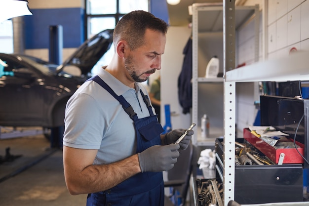 Widok z boku portret brodatego mechanika samochodowego wybierającego narzędzia podczas naprawy pojazdu w sklepie garażowym, miejsce na kopię