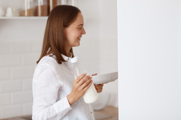 Widok z boku portret ciemnowłosej młodej dorosłej kobiety w białej koszuli, patrząc uśmiechnięty wewnątrz lodówki, trzymając talerz w rękach, znajduje posiłek na śniadanie rano.