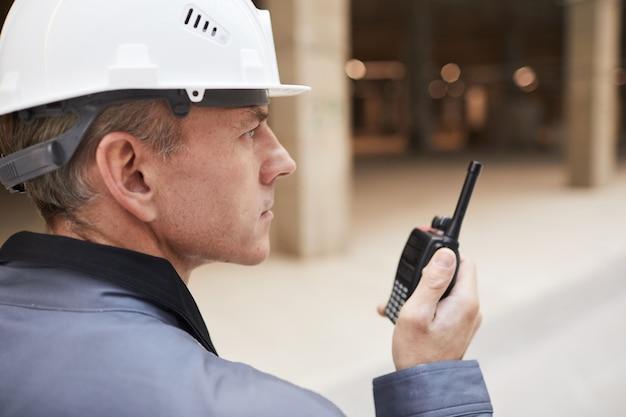 Widok z boku portret dojrzałego pracownika mówiącego przez walkie-talkie podczas nadzorowania pracy na budowie lub w warsztacie przemysłowym