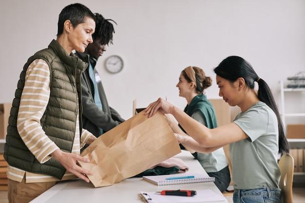 Widok z boku portret dojrzałej kobiety dającej torbę wolontariuszom podczas akcji pomocy i darowizn, miejsce kopiowania