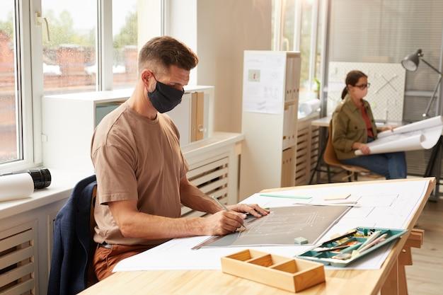 Widok z boku portret dojrzały brodaty architekt noszenie maski siedząc przy biurku rysunkowym w słońcu