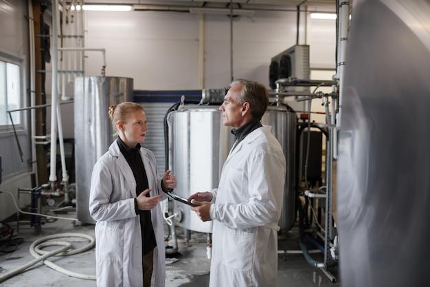 Widok z boku portret dojrzały mężczyzna instruujący pracownicę podczas omawiania pracy w fabryce produkcji żywności, miejsce na kopię