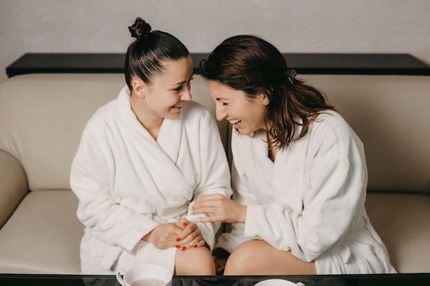 Widok z boku portret dwóch dziewczyn śmiejących się po masażu spa ubranych w szlafroki w centrum odnowy biologicznej spa.
