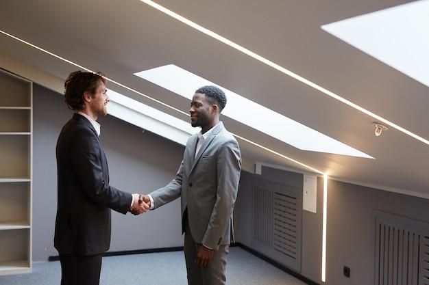 Widok z boku portret dwóch przystojnych biznesmenów, ściskających ręce po udanej transakcji, stojąc w pustej przestrzeni biurowej z oknami świetlików, kopia przestrzeń