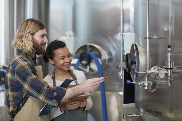 Widok z boku portret dwóch uśmiechniętych młodych pracowników kontrolujących produkcję w nowoczesnym browarze rzemieślniczym, kopia przestrzeń