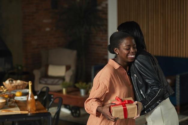 Widok z boku portret eleganckiej afroamerykanki przytulającej przyjaciela, witając gości na przyjęciu w domu,