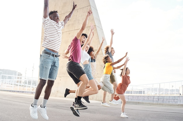 Widok z boku portret grupy szczęśliwych wieloetnicznych przyjaciół bawiących się młodych studentów skaczących na zewnątrz