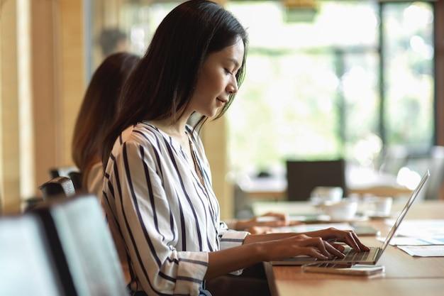 Widok z boku portret kobiety biznesu, która czuje się szczęśliwa ze swojej pracy z ogólnym laptopem w biurze, rozmyte tło