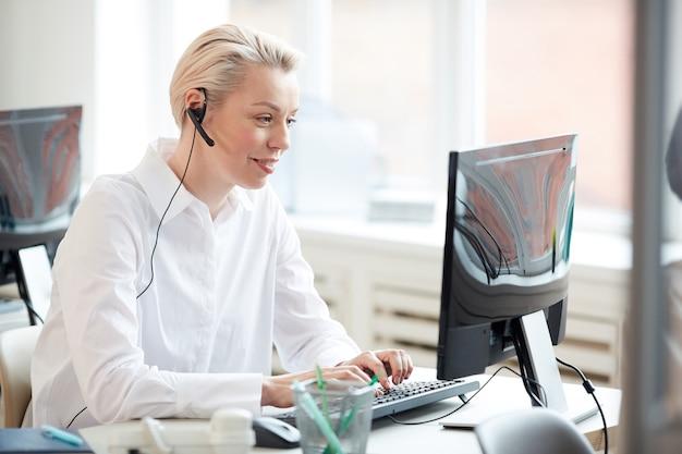 Widok z boku portret kobiety operatora infolinii za pomocą laptopa i noszącego zestaw słuchawkowy podczas wykonywania obsługi klienta