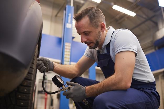 Widok z boku portret mechanika samochodowego sprawdzającego ciśnienie w oponach podczas kontroli pojazdu w sklepie garażowym, miejsce na kopię