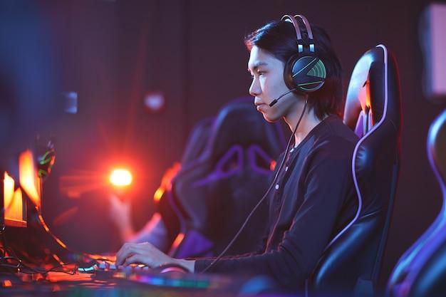 Widok z boku portret młodego azjatyckiego pro-gracza grającego w gry wideo w ciemnym pokoju, miejsce