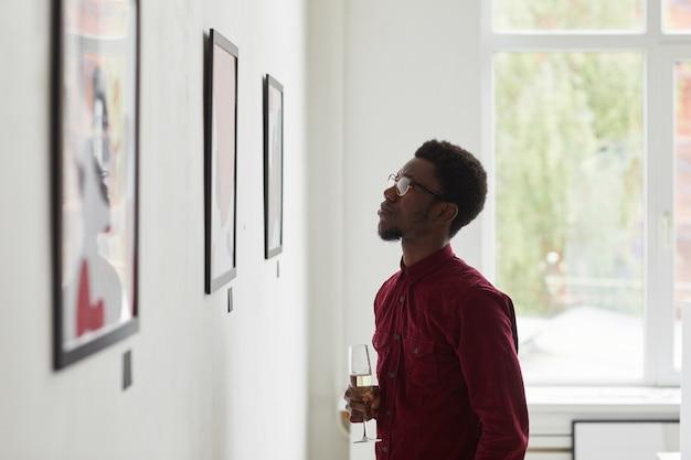 Widok z boku portret młodego mężczyzny afroamerykańskiego patrząc na obrazy i trzymającego kieliszek do szampana podczas otwarcia galerii sztuki,