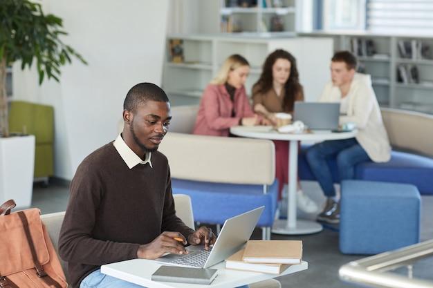 Widok z boku portret młodego mężczyzny afroamerykańskiego za pomocą laptopa w bibliotece uczelni z ludźmi w tle