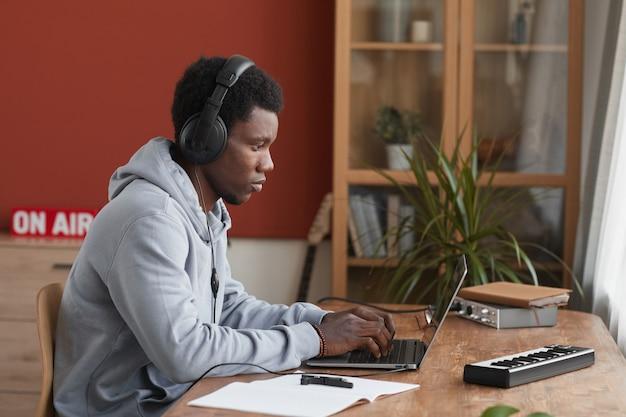 Widok z boku portret młodego muzyka afroamerykańskiego za pomocą laptopa podczas komponowania muzyki w domu, kopia przestrzeń