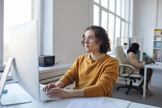 Widok z boku portret młodego programisty korzystającego z komputera podczas pracy przy biurku w białym wnętrzu biurowym, kopia przestrzeń