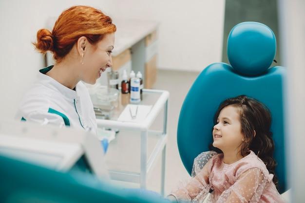 Widok z boku portret młodego stomatologa rozmawiającego z nim małym przyszłym pacjentem w stomatologii dziecięcej.