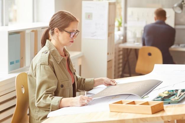 Widok z boku portret młodej architekt kobieta patrząc na plany, siedząc przy biurku rysunkowym w słońcu
