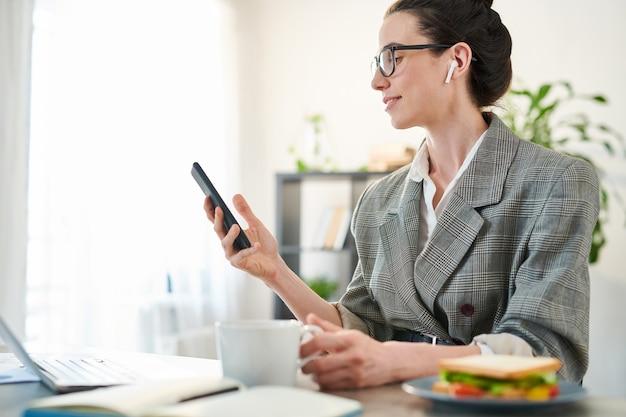 Widok z boku portret młodej bizneswoman przy użyciu smartfona w miejscu pracy i uśmiechnięta, kopia przestrzeń