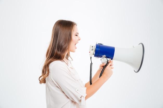 Widok z boku portret młodej kobiety krzyczącej w megafonie na białym tle na białej ścianie