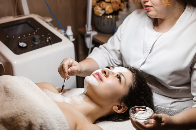 Widok z boku portret młodej kobiety uroczej robi maseczkę na twarz w centrum odnowy biologicznej spa przez kosmetyczkę.
