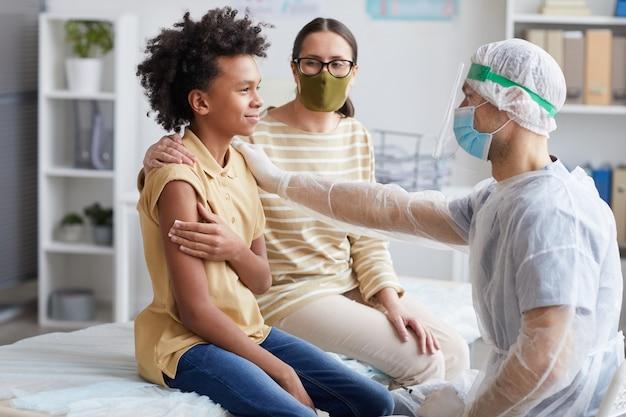 Widok z boku portret nastoletniego, afroamerykańskiego chłopca uśmiechającego się po szczepieniu przeciw pasożytowi w klinice z gratulacjami dla pielęgniarza