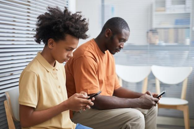 Widok z boku portret nastoletniego afroamerykańskiego chłopca za pomocą smartfona podczas oczekiwania w kolejce w klinice medycznej z tatą, miejsce kopiowania