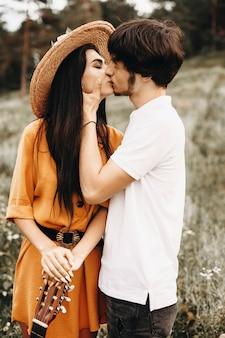 Widok z boku portret niesamowitej pary całującej się, podczas gdy mężczyzna dotyka twarzy swojej dziewczyny, podczas gdy ona trzyma gitarę na zewnątrz podczas randki.
