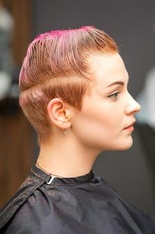 Widok z boku portret pięknej młodej kobiety rasy kaukaskiej z krótką różową fryzurą, czekając na fryzjera w salonie piękności