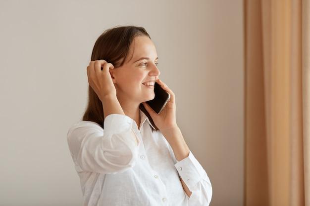 Widok z boku portret pozytywnej kobiety stojącej w pobliżu okna z beżowymi zasłonami, młoda dorosła dziewczyna ubrana w białą bawełnianą koszulę rozmawia przez telefon komórkowy, słysząc dobre wieści.
