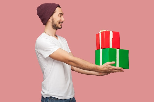 Widok z boku portret przyjazny przystojny brodaty młody człowiek hipster w białej koszuli i dorywczo kapelusz stojący, dając dwa obecne pudełko, uśmiech ząb. wewnątrz, na białym tle, studio strzał, różowe tło