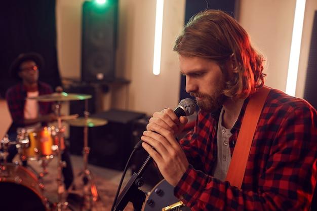 Widok z boku portret przystojny brodaty mężczyzna śpiewa do mikrofonu podczas próby
