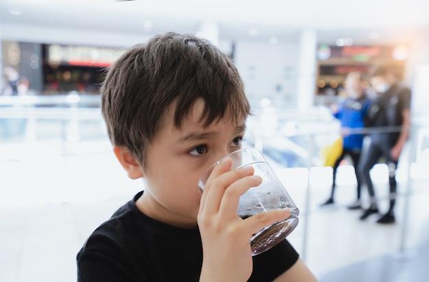 Widok z boku portret rasy mieszanej młode dziecko siedzące na stole, picie zimnego napoju w restauracji, toodler picie sody lub napój bezalkoholowy ze szkła, chłopiec dziecko czeka na foo w kawiarni