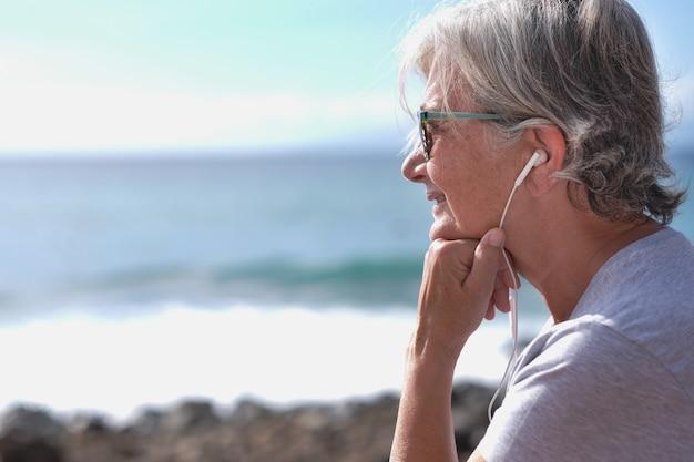 Widok z boku portret senior uśmiechający się kobiety siedzącej na plaży, słuchając muzyki przez słuchawki. siwe włosy kobieta relaksujący patrząc na horyzont nad morzem.