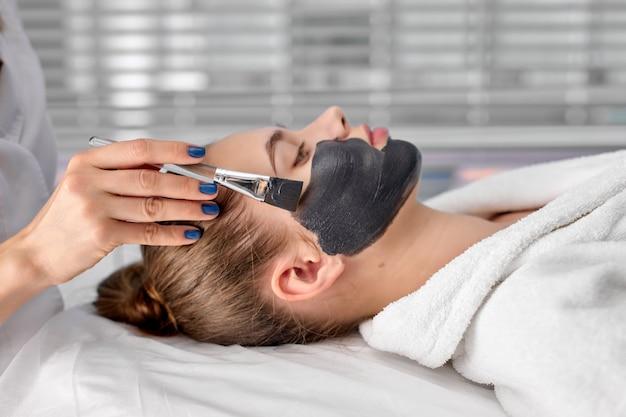 Widok z boku portret spokojna, atrakcyjna młoda kobieta korzystająca ze spa, leżąca na stole do masażu