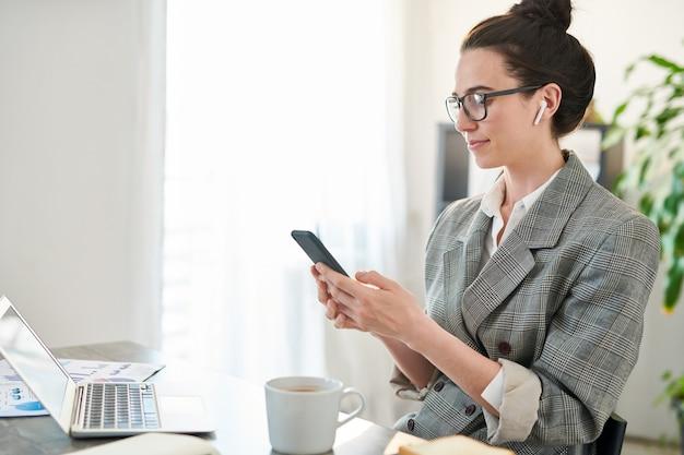 Widok z boku portret uśmiechnięta bizneswoman przy użyciu smartfona w miejscu pracy w biurze, kopia przestrzeń