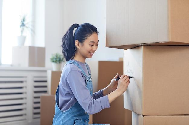 Widok z boku portret uśmiechniętej azjatyckiej kobiety piszącej na kartonach, etykietując je do przeprowadzki do nowego domu