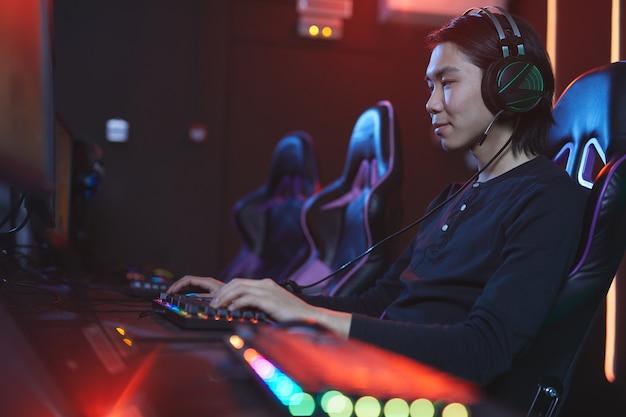 Widok z boku portret uśmiechnięty azjatycki mężczyzna grając w gry wideo w studio pro-gaming, kopia przestrzeń