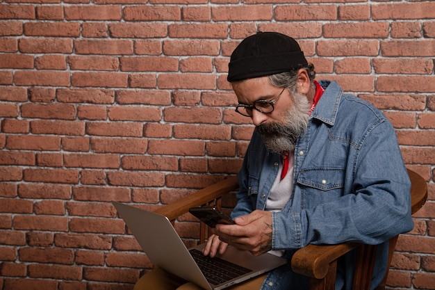 Widok z boku portret wesoły brodaty brunet w dżinsowej koszuli, pracujący na laptopie i telefonie komórkowym, wpisując e-mail lub rozmawiając w sieci społecznościowej, szczęśliwy wyraz twarzy.
