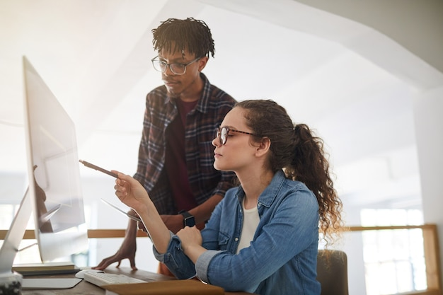Widok z boku portret współczesnej młodej kobiety wskazującej na ekran komputera podczas pracy z afroamerykańskim kolegą w biurze, koncepcja żeński programista it, miejsce na kopię