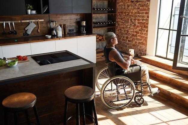Widok z boku portret współczesnej wytatuowanej kobiety na wózku inwalidzkim, cieszącej się kawą w domu i patrzącej na okno, kopia przestrzeń