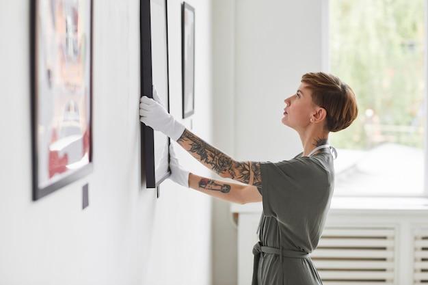 Widok z boku portret wytatuowanej kreatywnej kobiety wiszącej obrazy na ścianie podczas planowania wystawy w galerii sztuki,