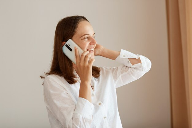 Widok z boku portret zadowolona szczęśliwa kobieta z prostymi ciemnymi włosami, ubrana w białą bawełnianą koszulę, stojąca z podniesionym ramieniem i rozmawiającym telefonem, odwracająca wzrok, mająca przyjemną rozmowę.