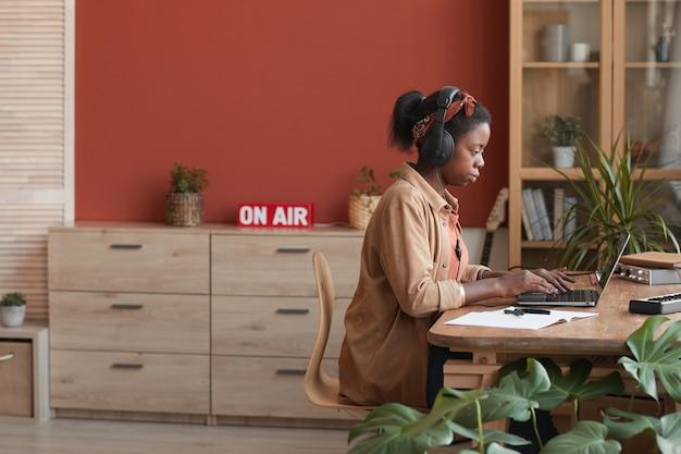 Widok z boku portret żeński muzyk afroamerykański za pomocą laptopa podczas komponowania muzyki w domu, kopia przestrzeń