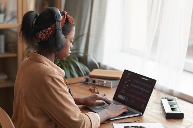 Widok z boku portret żeński muzyk afroamerykański za pomocą laptopa z oprogramowaniem do edycji dźwięku podczas komponowania muzyki w domu, kopia przestrzeń